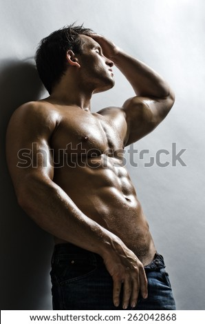 the very muscular handsome sexy guy on   grey wall  background - stock photo