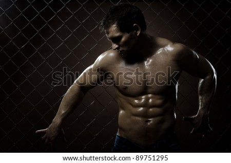 the very muscular handsome sexy guy ,  on  netting   steel fence