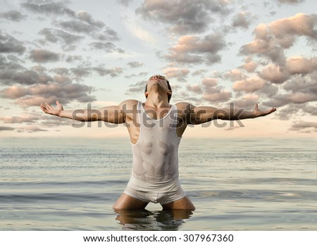 the very muscular handsome sexy guy on sky and sea background - stock photo