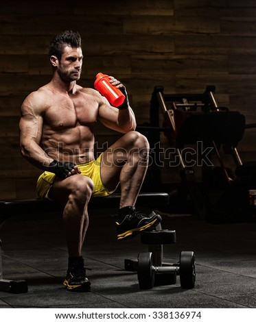 the very muscular sporty guy drinking protein in dark weight room, naked torso - stock photo