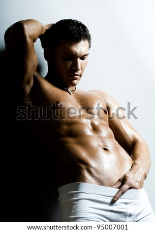 the very muscular  undressed handsome sexy guy on light-blue-grey  background - stock photo