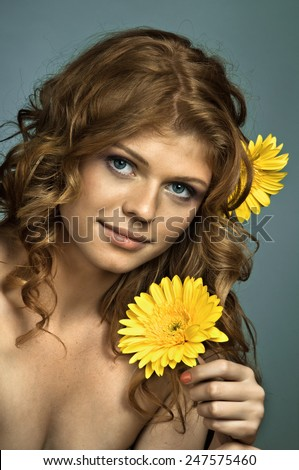 the very  pretty red-haired blue eyed young woman  with yellow flower,  smile , vertical close up portrait - stock photo