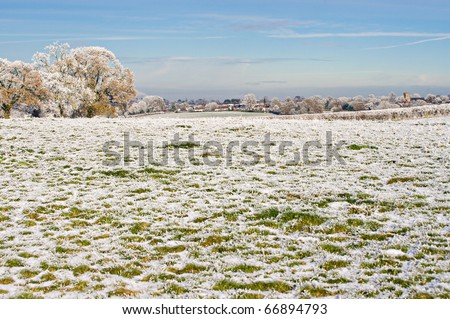 the view across frosty fields toward the village - stock photo