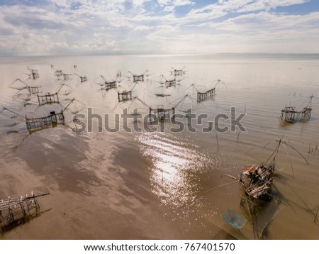 The view from above of a group of the conventional fishing style called Lift nets, used to trap fishes in a glittering lagoon with reflections from the sun ray