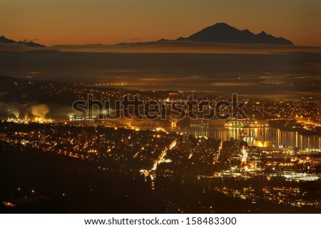 The view from the Cypress Mountain lookout of Vancouver and Burrard Inlet. The silhouette of Mount Baker in Washington State rises in the background. British Columbia, Canada.  - stock photo
