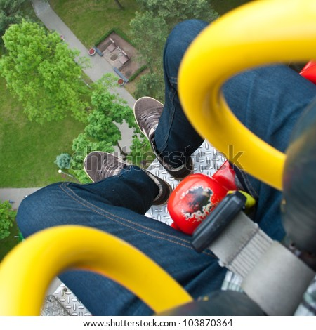 The view from the height of the Ferris wheel. Men's feet. - stock photo