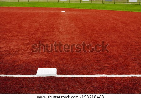 The view is from behind first base looking towards second base with artificial turf at a school softball field. The bright colors of the artificial turf are a high contrast to a normal playing field. - stock photo