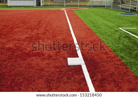 The view is from behind third base looking towards home plate with artificial turf at a school softball field. The bright colors of the artificial turf are a high contrast to a normal playing field.