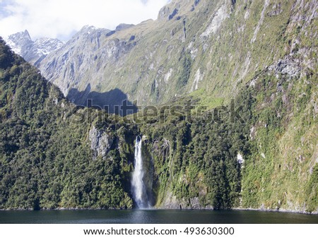 The view of a waterfall surrounded by mountains in Milford Sound (Fiordland National Park, New Zealand).