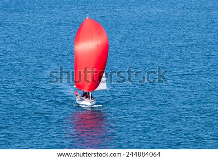The view of a yacht with a bright red sail in Marmaris resort town (Turkey).