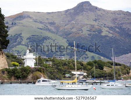 The view of Akaroa resort town marina with a lighthouse (New Zealand).