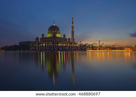 The view of one of the grand mosques in Putrajaya, Putra Mosque during early morning with its reflection on the lake.