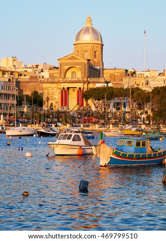The view of  St Joseph church on the shore and a traditional maltese boats (Luzzu) in the Kalkara bay between Birgu and Kalkara peninsular, Malta.