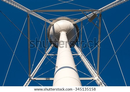 The view of the intricate lattice steel work underneath a white water tower. - stock photo