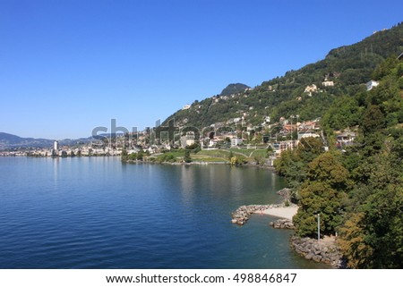 the view of the lake and shoreline with trees and city