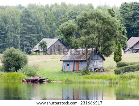 The view of the old wooden bathhouse under the tree in Lithuanian countryside.