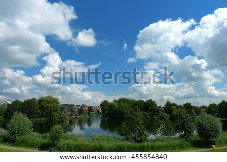 The view of vivid blue sky and white clouds contrast with green garden and field along the way in Europe  - stock photo