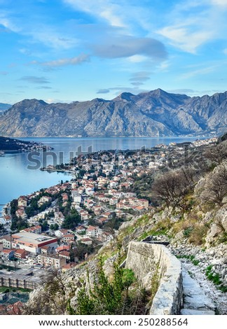 The view over the town of Kotor, Montenegro, the bay and the mountains from the ancient fortress wall up the mountain slope - stock photo