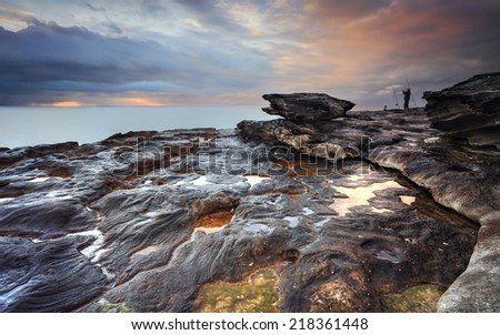 The view south from South Curl Curl rocks, NSW Australia.   Stormy skies over ocean and rocks and just after sunrise.  A fisherman clenches fists in jubilation while looking skyward - stock photo
