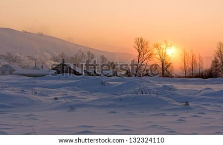 The village is covered with snow, lit the rising sun. - stock photo