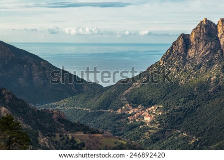 The village of Ota in Corsica with mountains and the Mediterranean sea behind - stock photo