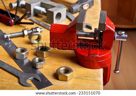 The vise to clamp on a wooden desktop environment tools - stock photo