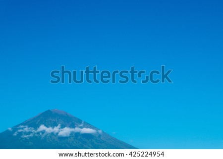 The volcano Gunung Agung dominating the horizon taken from Amed against a clear blue sky, a little fishing village located on the east coast of Bali, Indonesia.