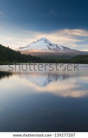 The volcano mountain Mt. Hood, in Oregon, USA. At sunset with reflection on the water of the Trillium lake.