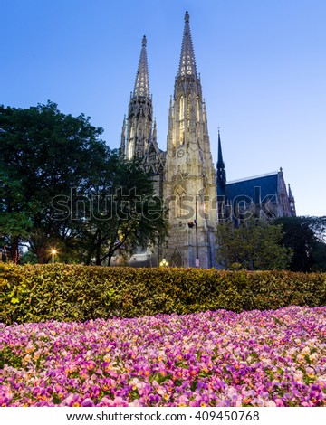 The Votive Church and purple spring flowers in Vienna at dusk - stock photo
