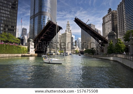 The Wabash Avenue bridge on the Chicago River is raised to allow the passage of sailboats on the final sail of the season from their harbor in Lake Michigan to their winter dry dock destination. - stock photo