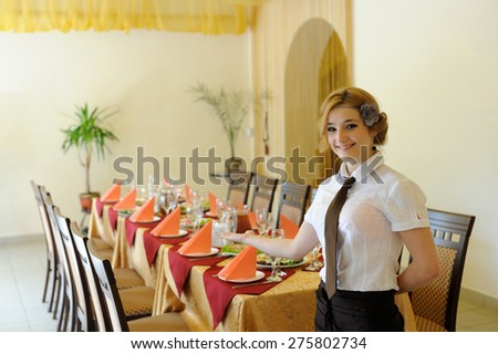 the waiter in the restaurant near served table - stock photo
