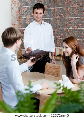 The waiter offers the menu to the visitors sitting at the table at the cafe