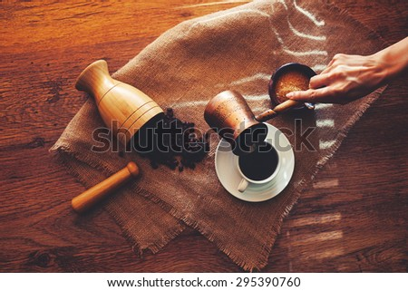 The waiter pours fresh coffee in a white cup and saucer that is standing next to a sugar bowl with brown sugar - stock photo