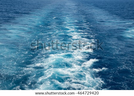 The wake of a cruise ship sailing on the ocean, with blue water and waves