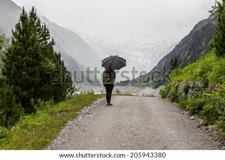 The walk with umbrella in the mountains - stock photo