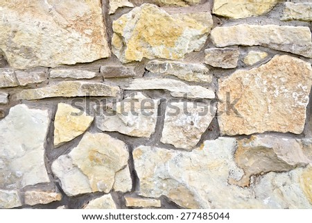 The wall, built of rough sandstone stones of various sizes, fastened with cement - stock photo