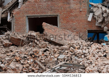 the wall collapsed houses after a disaster, earthquake, empty window door