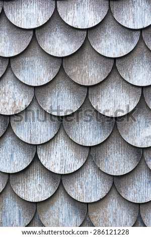 The wall covered with wooden shingles - wooden background.  - stock photo