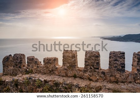 The wall of an ancient fortress in Alanya, Turkey. Beautiful summer landscape with sea view at sunset - stock photo