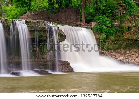 The wall of an old mill can be seen atop Indiana's Upper Cataract Falls. Photographed with a long exposure for silky smooth whitewater. - stock photo