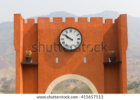 The wall with big clock in mountain background.