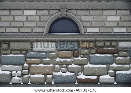 the wall with small window, decorative imitation rubble and bricks - stock photo