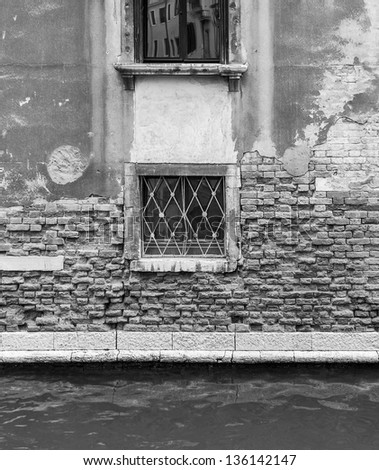The wall with windows of the medieval house on the canal - Venice, Italy (black and white)