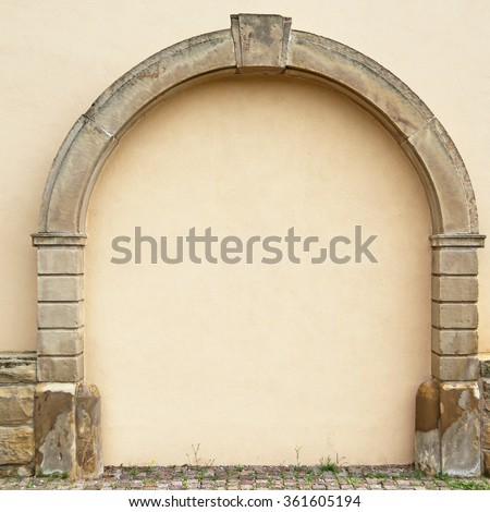 The walled-up door with stone arch  on the ancient beige plastered walls background, photo frame, place for text - stock photo