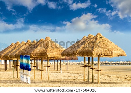 The warm rays of sunshine in late spring are projected on a deserted beach still awaiting the summer with tourists.