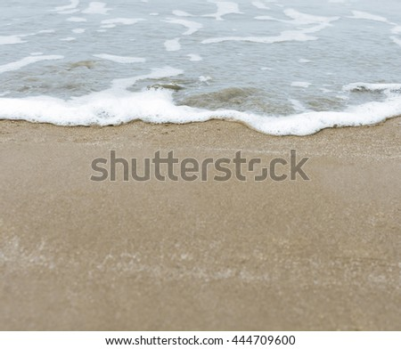 The wash of the blue British sea tide meeting the wet beach sand. - stock photo