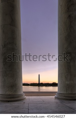 The Washington Monument framed between pillars of the Jefferson Memorial at dawn.