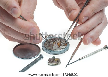 the watchmaker with tweezers and a screw-driver repairing an old pocket watch