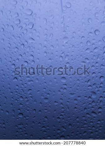 The water drops on glass in blue tone background