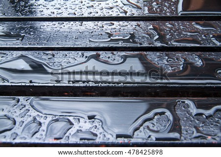 The water drops on wooden garden table.